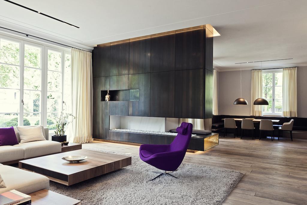 Den Wohnbereich dominiert ein dunkler Stahlkamin mit integriertem Flatscreen-TV, der Dielenboden besteht aus bayerischer Eiche