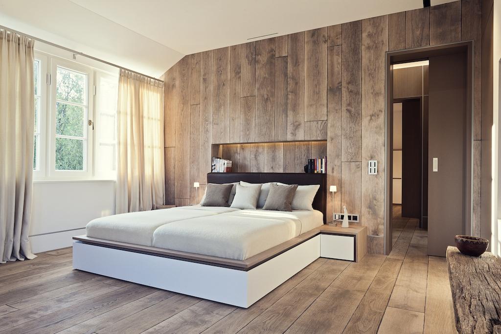 Das Schlafzimmer erinnert an Winterurlaube in Kitzbühel – Holzdielen, die an den Wänden nach oben gezogen sind, zaubern Hüttenflair