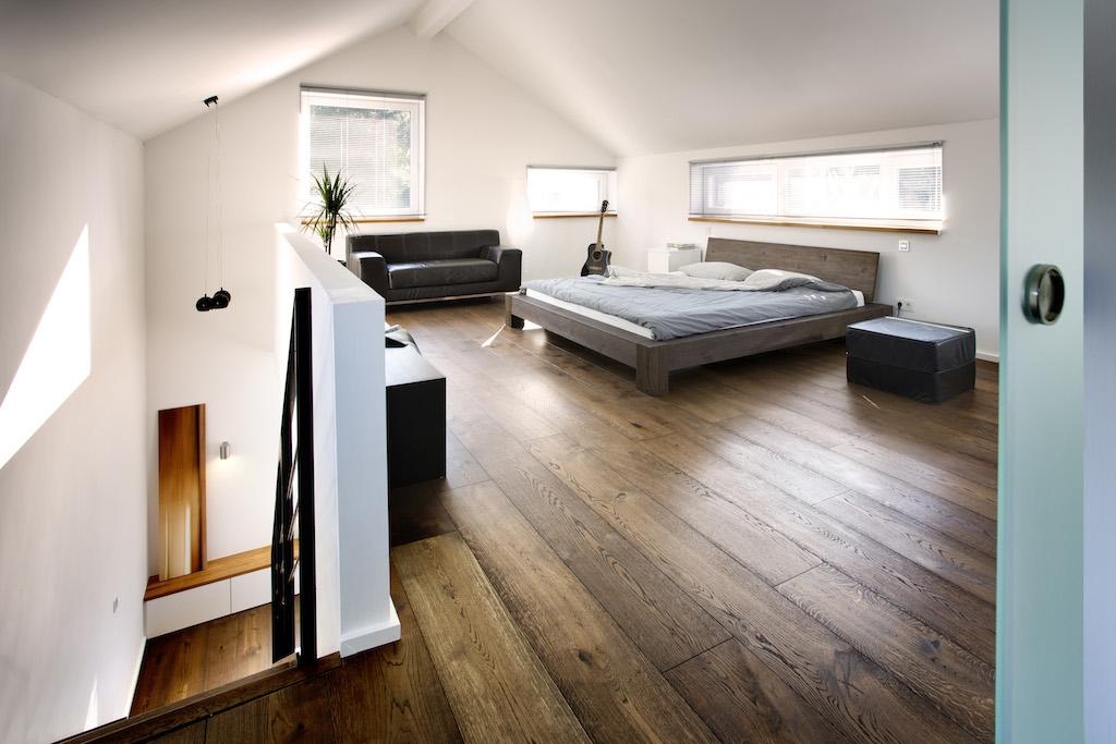 Einen Großteil des Obergeschosses nimmt das Schlafzimmer ein, das trotz schmaler Fensterbänder hell und luftig wirkt