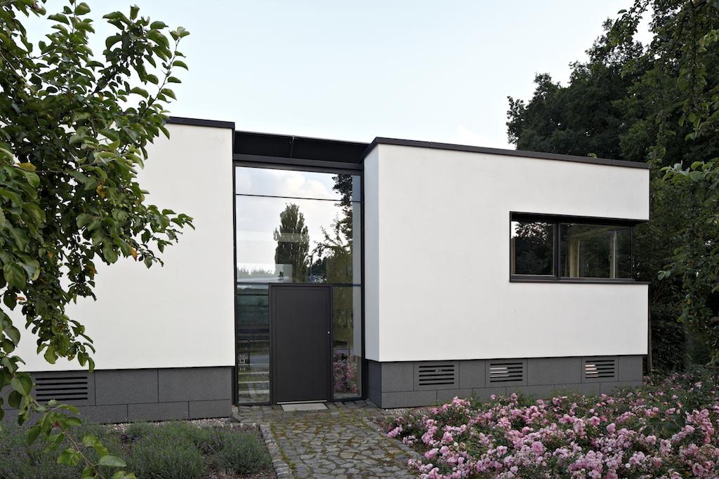Zur Straße hin ist das Gebäude deutlich geschlossener ausgeführt. Die Fensterbänder laufen über Eck und sind mit Ganzglasecken ausgeführt
