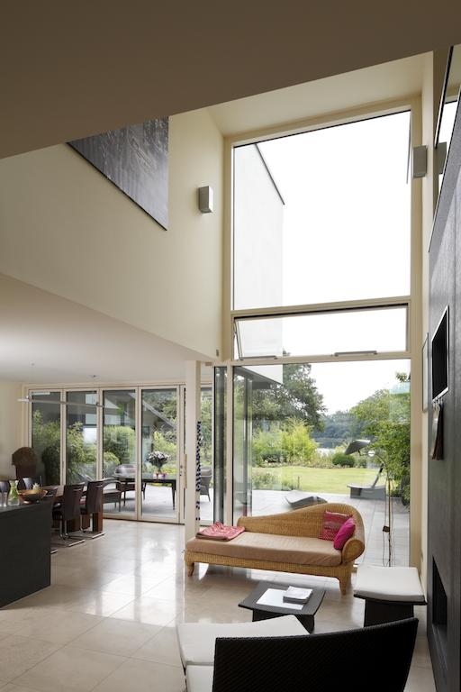 Die Wohnhalle mit Zutritt zur Terrasse und Blick auf den Plauer See: Automatisch gesteuerte Senkklappflügel und Dachluken sorgen für sommerliche Querlüftung