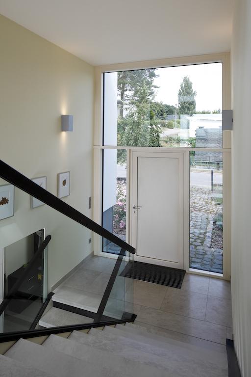 Über den Eingangsbereich werden die beiden obergeschossigen Bauteile und die tiefer gelegene Wohnhalle zentral erschlossen. Die Eingangstür ist mit einem biometrischen Zutrittssystem ausgestattet
