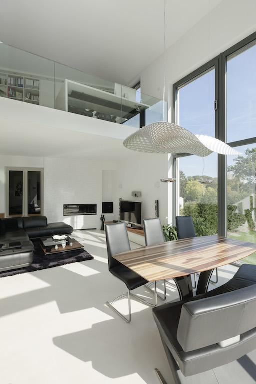 Die zweite Ebene im Wohnquader ist mit nur 2,40 m Raumhöhe bewusst flach gehalten – das steht im schönen Kontrast zum offenen Wohnbereich. Mit einer Glasbrüstung öffnet sich die Galerie mit Büro in den Raum
