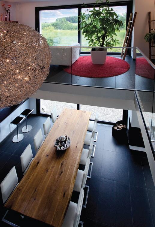 Im Zentrum des Hauses steht ein riesiger Holztisch für 10 Personen. Von der Galerie oben hat man einen schönen Blick in den Wohnbereich