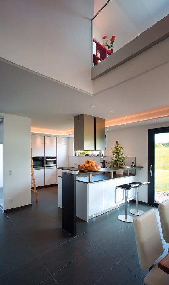 Ein dunkler Nero Assoluto wird als Küchenarbeitsplatte genutzt und zieht sich durchs ganze Haus – er findet sich wieder am Kamin und in den Badmöbeln