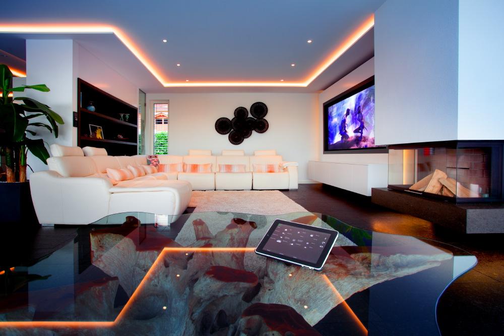 Die Unterhaltungselektronik in der Sofaecke ist bei Nichtbenutzung komplett unsichtbar – Leinwand, Beamer und Lautsprecher bringen Kinofeeling ins Haus