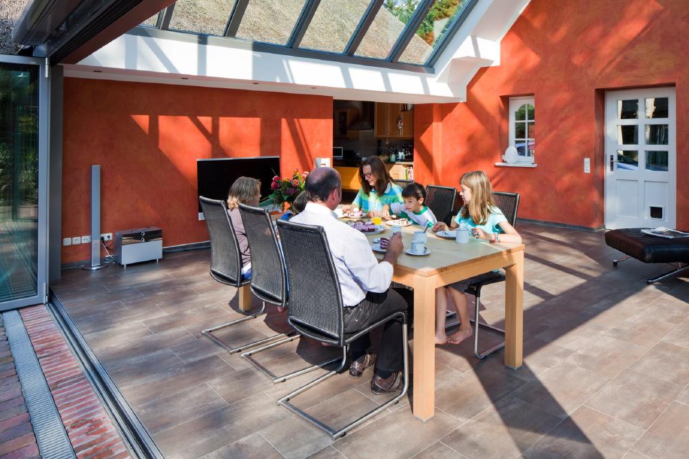 Seit es den Wintergarten gibt, nutzt die Familie das Wohnhaus fast nur noch zum Kochen und Schlafen. Über die offene Küche sind Haus und Wintergarten direkt miteinander verbunden