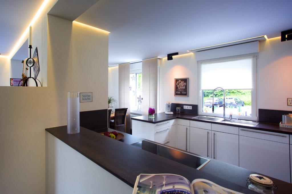Das Innere ist hell und offen, die Küche geht ums Eck in den Wohnbereich über. Für Behaglichkeit sorgt ein Kamin im Zentrum.