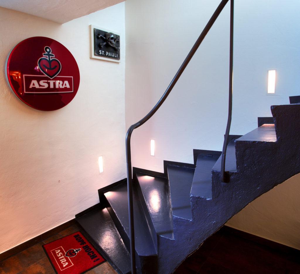 Die Liebe zu Hamburg spiegelt sich in vielen Details wieder, beispielsweise in den glänzenden Metallplatten mit Namen berühmter St. Pauli-Bars im Boden oder Astra-Werbeschildern.