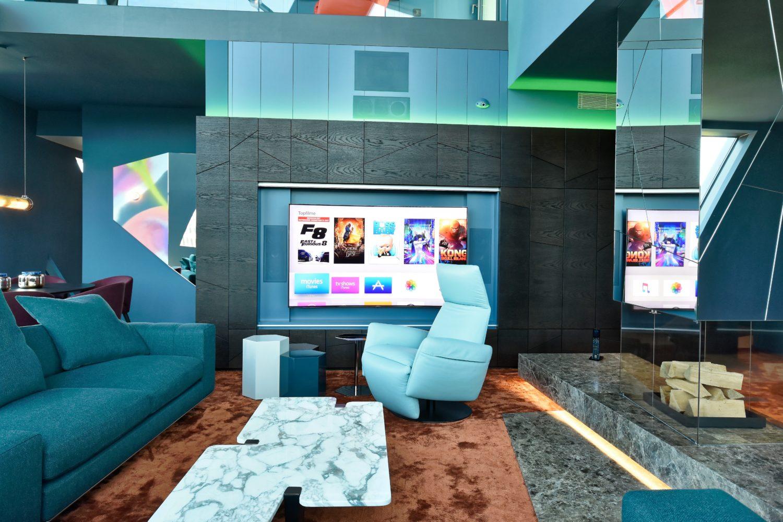 Der großformatige TV-Bildschirm verschwindet bei Nichtbenutzung hinter der handgefertigten Vertäfelung, die Architekturelemente aufnimmt